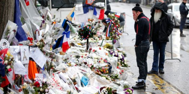 Jesse Hughes (L) and Dave Catching, members of Eagles of Death Metal band, mourn in front of the Bataclan...