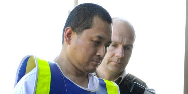 Vince Weiguang Li (L), suspect in the murder of Tim McLean aboard a Greyhound bus in Manitoba, is escorted by sheriff officers on his way to a court appearance in Portage la Prairie August 5, 2008. REUTERS/Fred Greenslade (CANADA)