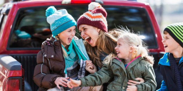 A happy mother with her three children outdoors in the fall, sitting on the back of a pickup truck, dressed for cool weather in jackets and winter hats.  They are laughing together, having a good time.