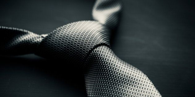 Soft focus photo of grey man's tie on dark background in the style of Fifty Shades of Grey.