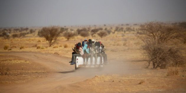 Migrants crossing the Sahara desert into Libya ride on the back of a pickup truck outside Agadez, Niger,...