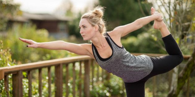 Beautiful young woman doing yoga on back porch in exercise clothes and yoga