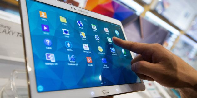 A customer tries out a Samsung Electronics Co. Galaxy Tab S tablet device on display at the company's...