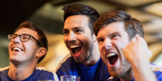 sport, people, leisure, friendship and entertainment concept - happy football fans or male friends drinking...