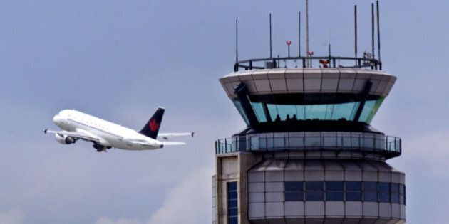 An Air Canada jet flies past the control tower at Montreal's Dorval International Airport, June 8. The...