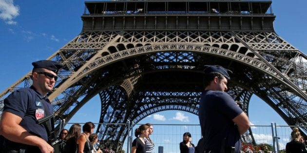 French CRS policemen patrol as tourists walk past in front of the Eiffel Tower in Paris, France August...
