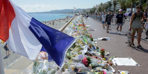 People walk past flowers left in tribute at a makeshift memorial to the victims of the Bastille Day truck...