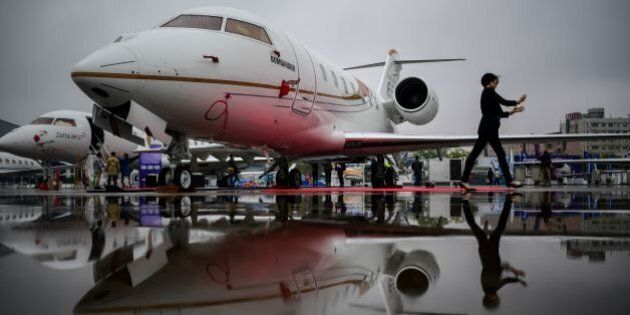 A woman walks past a Bombardier Challenger 650 business jet before the start of the 2017 Asian Business...