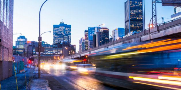 This is a horizontal, color, royalty free stock photograph of downtown rush hour traffic along Autoroute Bonadventure in Montreal an urban travel destination in Quebec, Canada. The city buildings are illuminated in the background as dusk turns to night. Buses and cars drive past on the street in a motion blur of light streaks. Photographed with a Nikon D800 DSLR camera.