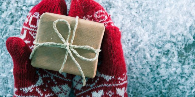 Female hands in winter gloves with christmas gift