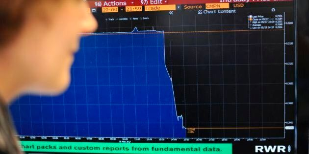 A journalist poses looking at the intraday price chart for the Brazilian real against the US dollar in...