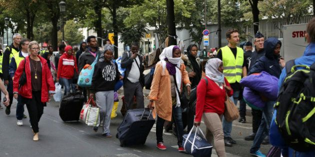 Migrants are evacuated from a camp in the north of Paris, Friday, Sept. 16, 2016. Police and city officials...