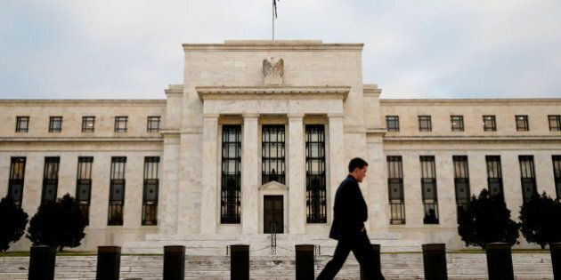 FILE PHOTO: A man walks past the Federal Reserve Bank in Washington, D.C., U.S. December 16, 2015. REUTERS/Kevin...
