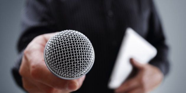 Hand holding a microphone conducting a business interview or press