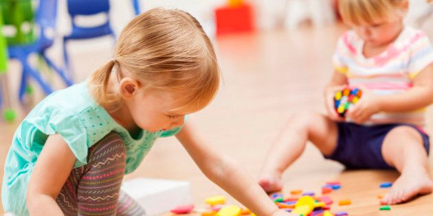 Two sweet Caucasian toddler girls playing with puzzle pieces on the floor of their preschool classroom....
