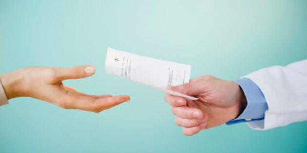 Close up of doctor's hand giving prescription to patient, studio