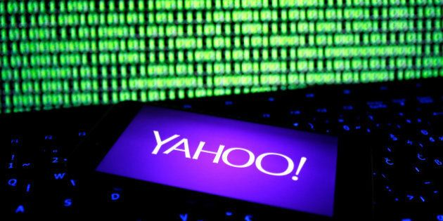 A photo illustration shows a Yahoo logo on a smartphone in front of a displayed cyber code and keyboard...