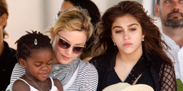 Pop star Madonna sits with her adopted Malawian child Mercy James and daughter Lourdes during a bricklaying...