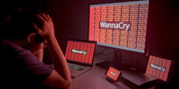 Young Asian male frustrated, confused and headache by WannaCry ransomware attack on desktop screen, notebook...