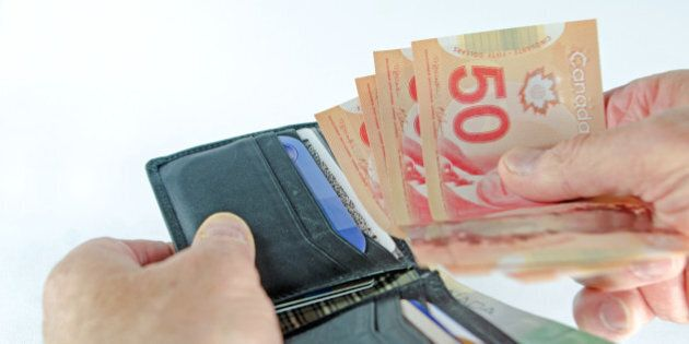 An used black leather wallet showingl a hand taking currency from it to make a purchase. Light background.