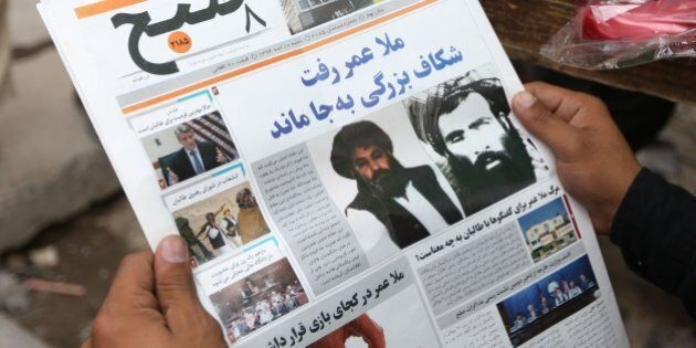 FILE - In this Saturday, Aug. 1, 2015 file photo, an Afghan man reads a local newspaper with photos of...