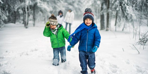 Mother and three kids having fun in forest on snowy day. Girl is aged 9 and boys are aged 6. The laughing...