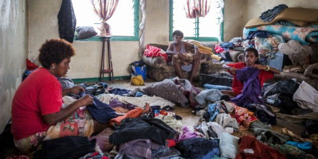 Fijian 10-year-old Lusiana (R) helps her grandmother (C) and aunt (L) sort through clothes in Rakiraki...