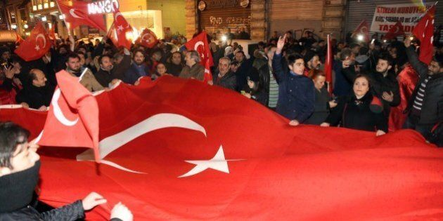 ISTANBUL, TURKEY - MARCH 12: Turkish people chant slogans and hold Turkish flags to protest Netherlands...