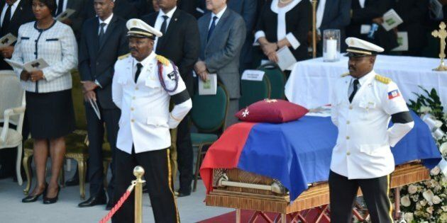 Police Officers from the National Palace stand next to the casket of former Haitian president Rene Preval...