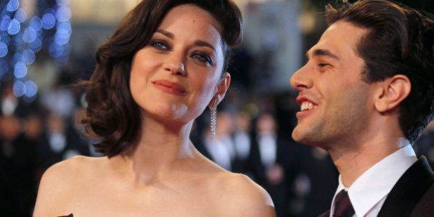 Director Xavier Dolan (R) and cast member Marion Cotillard pose on the red carpet as they arrive for the screening of the film