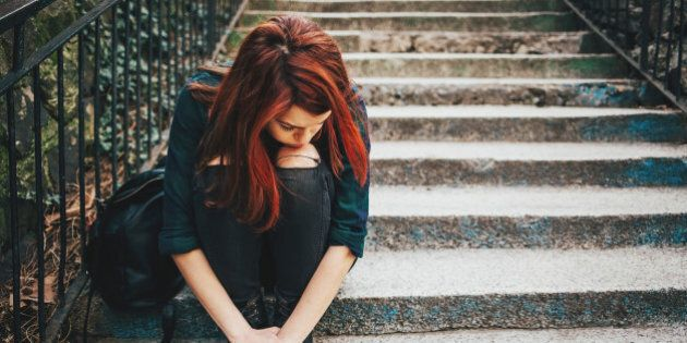 Depressed young woman sitting on stairs outdoors, with copy