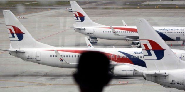 A man views a fleet of Malaysia Airline planes on the tarmac of the Kuala Lumpur International Airport,...