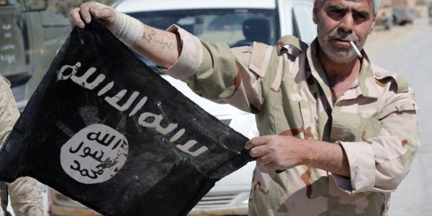 A Syrian soldier displays on April 4, 2016 an Islamic State (IS) group flag after Syrian troops regained...