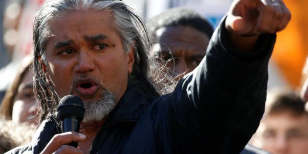 Immigration activist Ravi Ragbir points at the U.S. Citizenship and Immigration Services offices building...