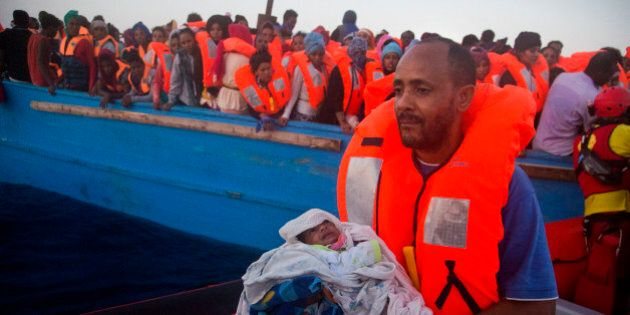 A man carries his five days old son after been rescued from a crowded wooden vessel as they were fleeing...