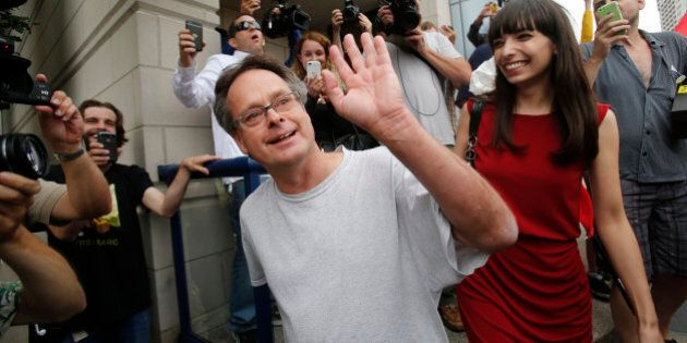 Marijuana advocate Marc Emery waves to his supporters as he walks with his wife Jodie following his release from an American prison for selling marijuana seeds in the U.S., in Windsor, Ontario August 12, 2014.    REUTERS/Rebecca Cook  (CANADA - Tags: DRUGS SOCIETY CRIME LAW)