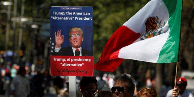 A man holds up a placard with an image of U.S. President Donald Trump during a march to protest against...