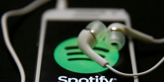 Earphones are seen on top of a smart phone with a Spotify logo on it, in Zenica February 20, 2014. Online...