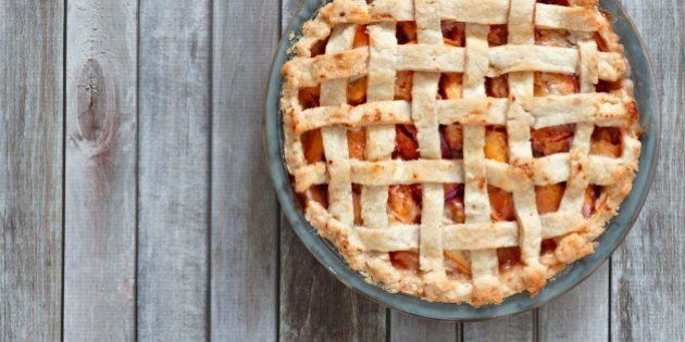 Rustic homemade peach pie in baking plate, above view on a wood