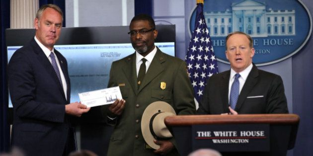 National Park Service Superintendent Tyrone Brandyburg (C) and Secretary of the Interior Ryan Zinke hold...