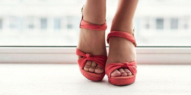 groomed female feet in red sandals on windowsill