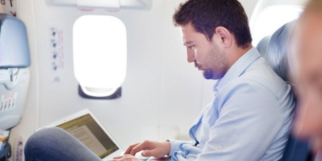Casually dressed middle aged man working on laptop in aircraft cabin during his business travel. Shallow...