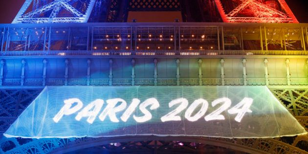 PARIS, FRANCE - FEBRUARY 03: The Eiffel tower is lit with the colours of the Olympic flag with the words...