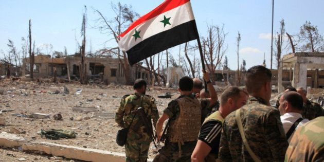 Forces loyal to Syria's President Bashar al-Assad walk at a military complex as one of them holds up...