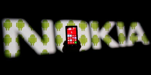 A man holding a Nokia Lumia 820 phone is seen through a Nokia logo with a background displaying Android...