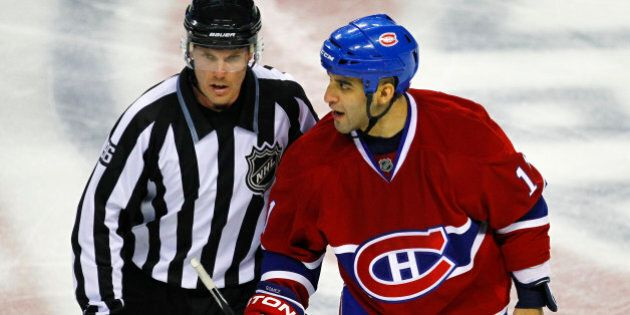 Montreal Canadiens center Scott Gomez is led to the penalty box by linesman David Brisebois during the...