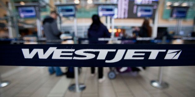 Westjet Airlines Ltd. signage is displayed on a band as travelers stand in line at Vancouver International...