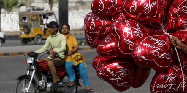 A couple on a motorcycle ride past a vendor selling heart-shaped balloons on Valentine's Day in Karachi,...
