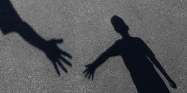 Helping Hand with a shadow on pavement of an adult hand offering help or therapy to a child in need as...