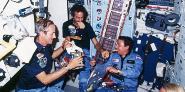 Astronauts eat a meal on board the Space Shuttle Discovery. Two of the astronauts hold slices of bread...